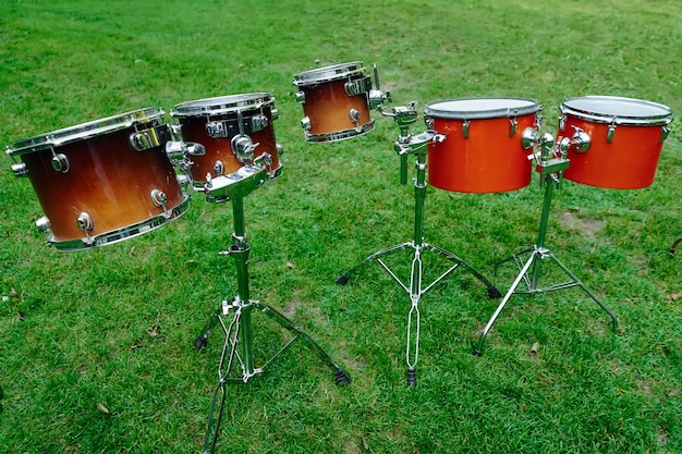 Drum kit on the street on a green lawn.