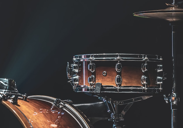 Drum set in a dark room with beautiful lighting, snare drum, cymbals, bass drum.