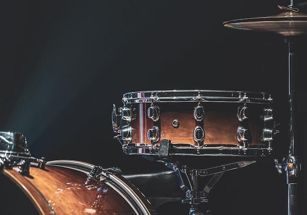 美しい照明、スネアドラム、シンバル、バスドラムのある暗い部屋に置かれたドラム。