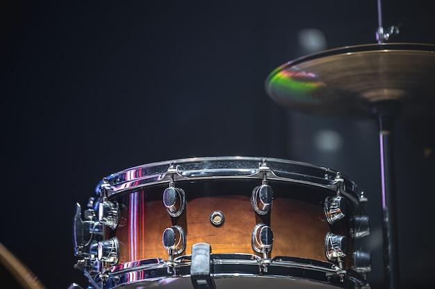 美しい照明、スネアドラム、シンバルのある暗い部屋に置かれたドラム。