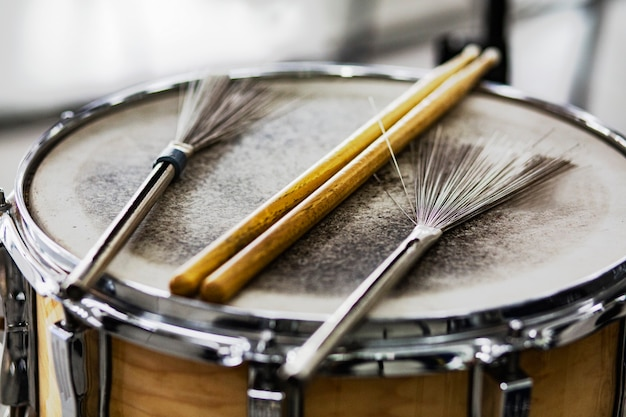 오래 된 가죽 드럼에 드럼 스틱과 와이어 브러쉬