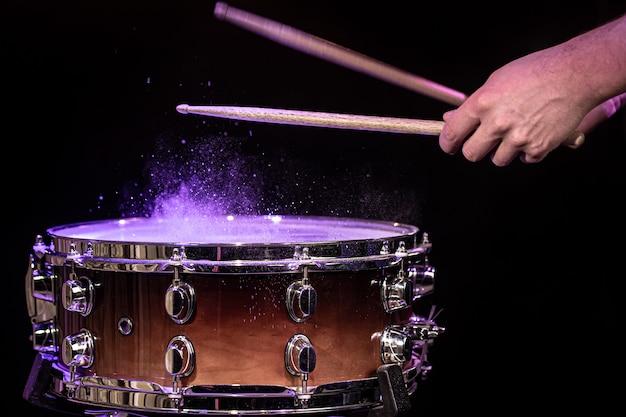 스튜디오 조명 아래 검은 공간에 물이 튀는 스네어 드럼을 치는 드럼 스틱을 닫습니다.