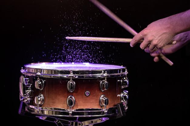 스튜디오 조명 아래 검은 벽에 물이 튀는 스네어 드럼을 치는 드럼 스틱을 닫습니다.