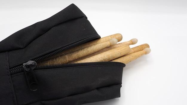 本物の木の素材とジッパー付きの黒い色の布製バッグから作られたドラムスティック