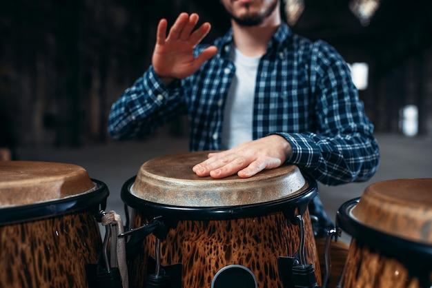 Барабанщик руки играет на деревянном барабане