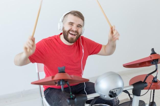 드러머, 취미 및 음악 개념 - 전자 드럼을 연주하는 빨간 셔츠에 젊은 남자 드러머.