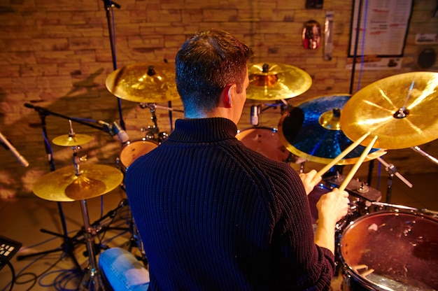Drummer playing on drum set on stage