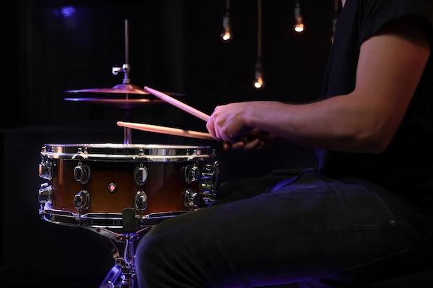 暗闇の中でスネアドラムにドラムスティックを演奏するドラマー。コンサートとライブパフォーマンスのコンセプト。