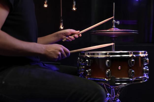 드럼을 연주하는 드러머는 어둠 속에서 스네어 드럼에 스틱. 콘서트 및 라이브 공연 개념.