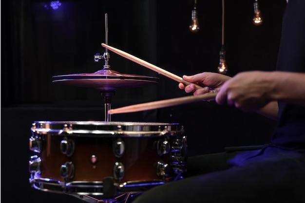 Барабанщик играет барабанными палочками на малом барабане в темноте. концепция концерта и живого выступления.