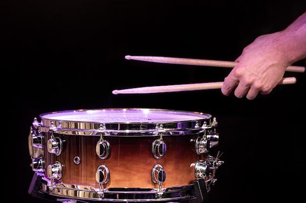 검은 색 바탕에 올 무 드럼에 드럼 스틱 재생 드러머를 닫습니다.