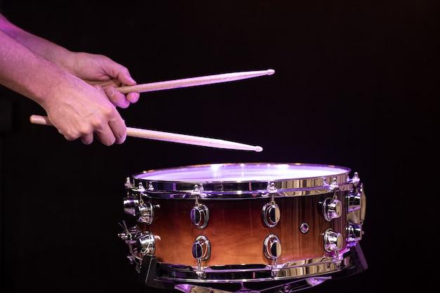 어두운 벽에 올 무 드럼에 드럼 스틱을 연주 드러머를 닫습니다.