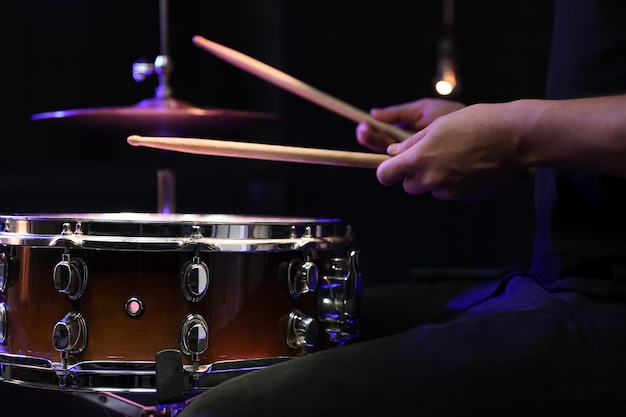 Drummer playing drum sticks on a snare drum in dark. concert and live performance concept.
