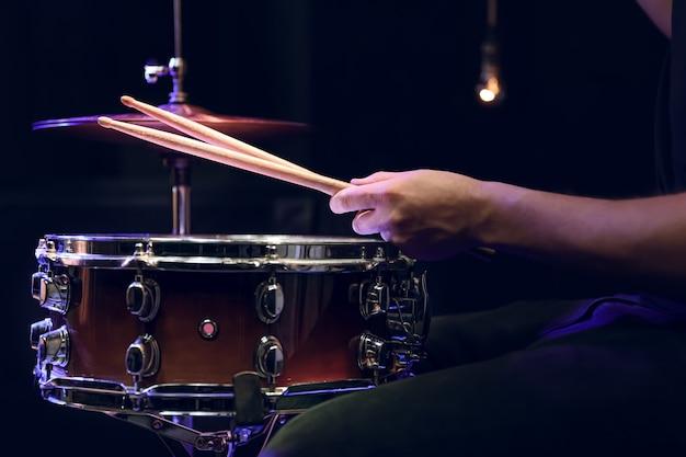 Batterista che suona bacchette su un rullante nel buio. concerto e concetto di performance dal vivo.