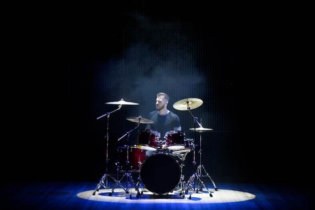Drummer playing the drums with smoke and powder