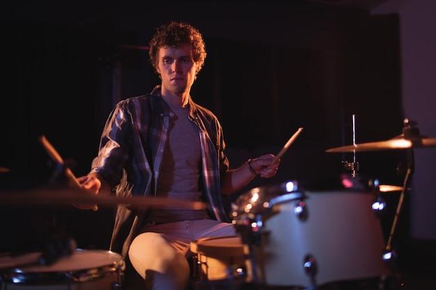 Барабанщик играет на барабанной установке