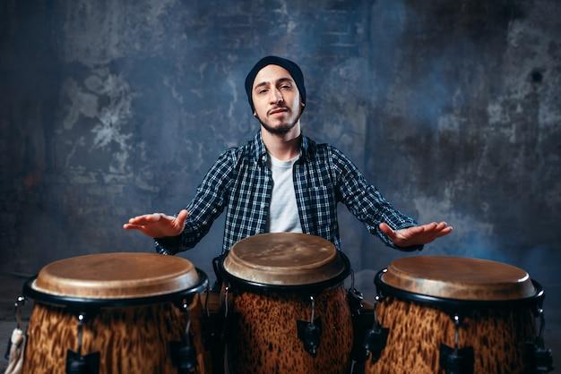 木製のボンゴドラムで演奏するドラマー、ビートミュージック
