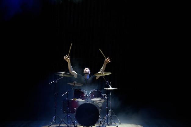 Барабанщик играет на барабанах на сцене