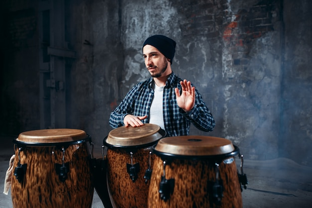 Drummer playing on wooden bongo drums in factory shop, beat rhythm