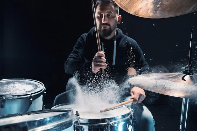 록 콘서트 전에 드럼 리허설을 하는 드러머. 밀가루 형태의 쇼 효과가 있는 스튜디오에서 드럼 세트로 음악을 녹음하는 남자