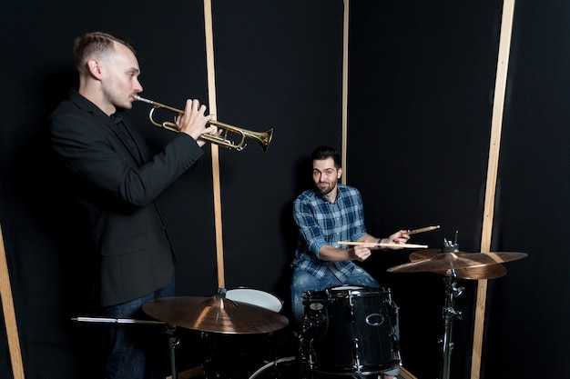 Drummer and trumpet player performing
