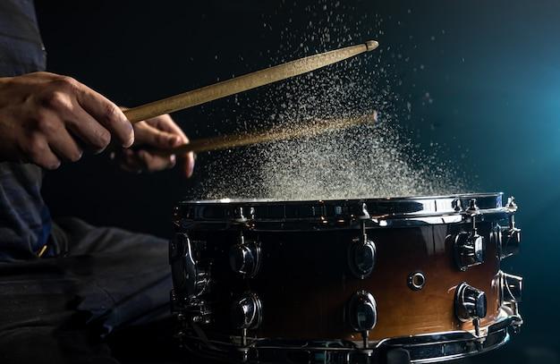 Drummer using drum sticks hitting snare drum with splashing water on black background under studio lighting close up.