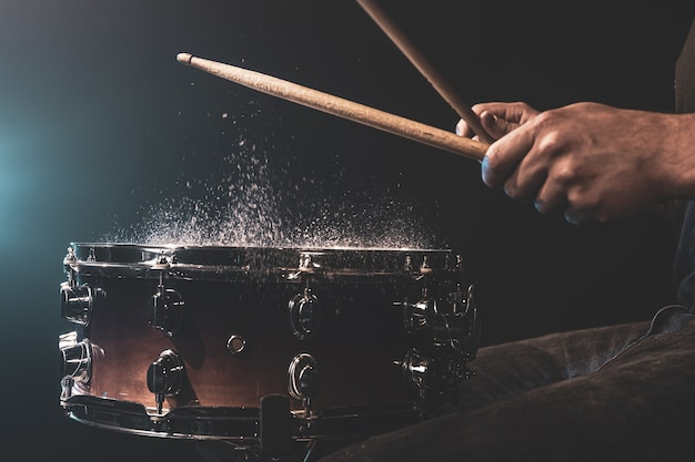드럼 스틱을 사용하는 드러머는 스튜디오 조명 아래 검은색 배경에 물이 튀는 스네어 드럼을 치고 있습니다.