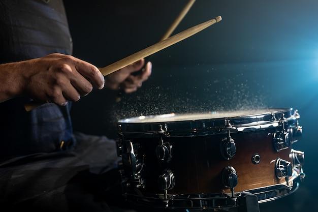 검은 배경에 물이 튀는 스네어 드럼을 치는 드럼 스틱을 사용하는 드러머