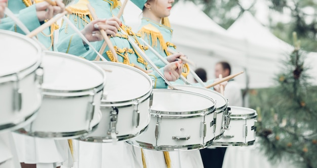 Drummers in green uniform stand in a row and drumming