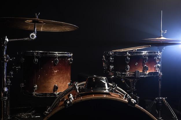ドラム、バスドラム、ハイハット、スポットライトからのビームを伴う暗い背景のシンバル、コピースペース。