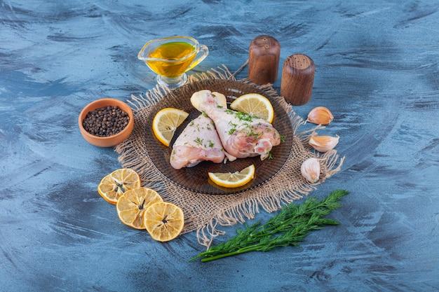 青い表面の黄麻布ナプキンの乾燥レモン、スパイスボウル、ディル、オイルの横にあるガラス板上のドラムスティックとレモン