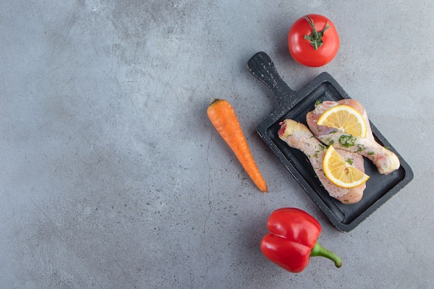 Голени и нарезанный лимон на доске рядом с овощами на мраморном фоне.