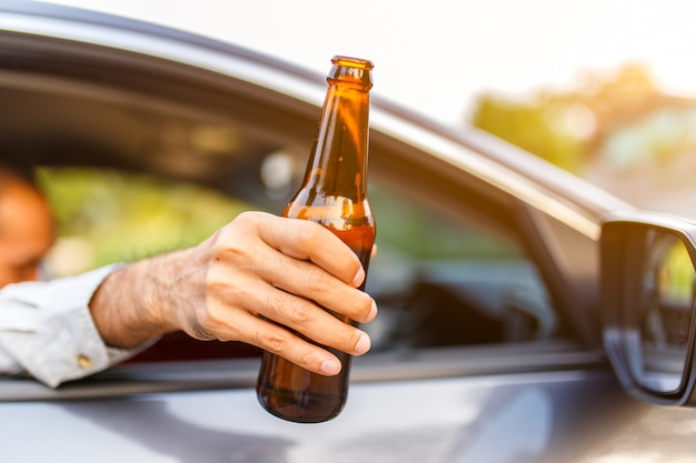 Drunk asian young man drives a car with a bottle of beer with sunset background