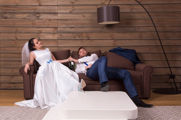 Drunk bride and groom relax on couch after wedding