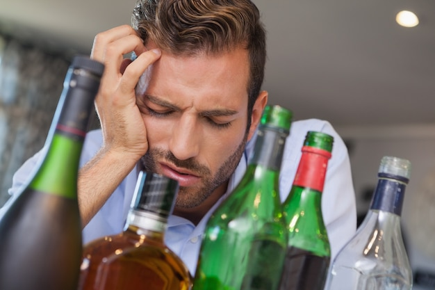 Drunk businessman slumped beside many spirit bottles