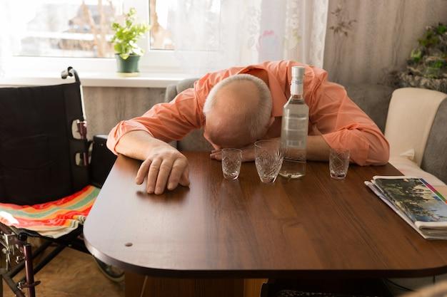 Пьяный старик-инвалид, сидящий рядом со своей инвалидной коляской, опираясь на деревянный стол в гостиной с бутылкой вина и бокалами наверху.
