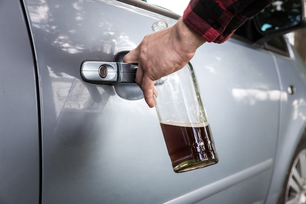 Drunk driver is opening the car door. man is holding a bottle and keys. alcohol while driving. accident from addiction problem.