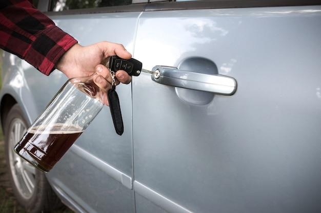 술 취한 운전자가 차 문을 열고 있습니다. 남자가 병과 열쇠를 들고 있다. 운전 중 술. 중독 문제로 인한 사고.