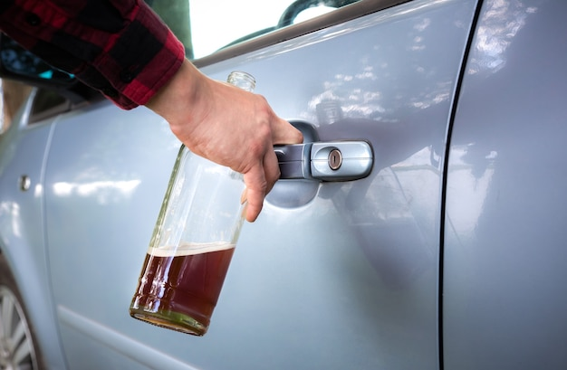 Пьяный водитель открывает дверь машины.