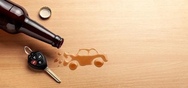 음주 운전. 알코올로 인한 고장난 자동차 사고. 맥주 병 및 자동차 키. 깨진 차.