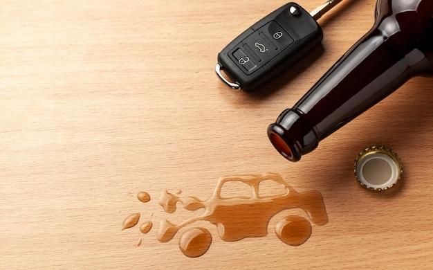 음주 운전. 알코올로 인해 부서진 자동차 사고. 맥주병과 자동차 열쇠. 부서진 차.