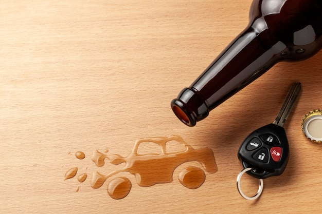 Drunk driving. accident with a broken car from alcohol. beer bottle and car keys. broken car.