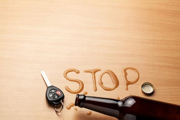 음주 운전. stop이라는 단어의 모양으로 맥주병과 엎질러진 맥주. 자동차 키.