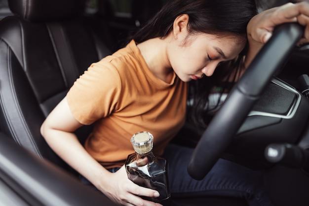 자동차에 취한 여성 운전자, 스티어링 휠 뒤에 여자의 손에 알코올 병-음주 운전의 개념