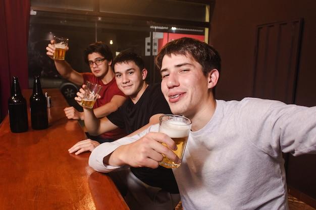Пьяные друзья делают селфи, попивая пиво в баре.