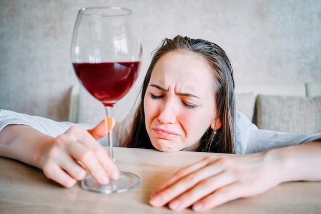 Пьяная девушка пьет вино и плачет над столом.