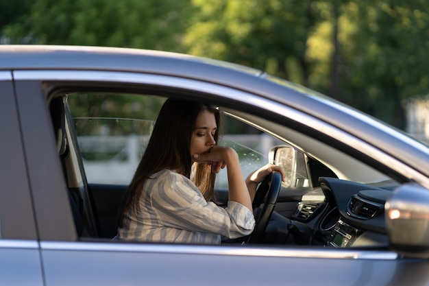 두통이나 인계로 고통받는 차량에서 불행한 피곤한 젊은 여성을 운전하는 술취한 소녀