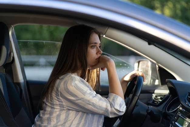 Drunk girl driving car unhappy tired young female in vehicle suffering from headache or handover