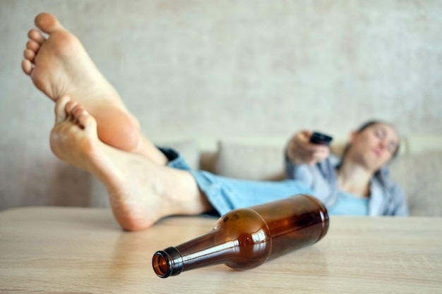 The drunk girl lies on a sofa switching channels on the tv, legs on the table