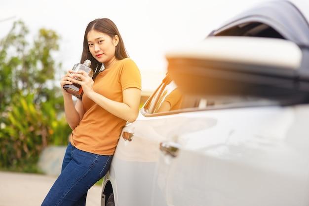 酔っ払いの女の子が手にボトルアルコールを持って車の横に立っている、車の近くに立っている間ウイスキーを飲む女性